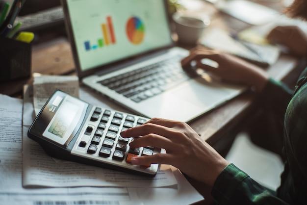Vrouw berekent de kosten van de rekening. ze drukt op de rekenmachine. Premium Foto