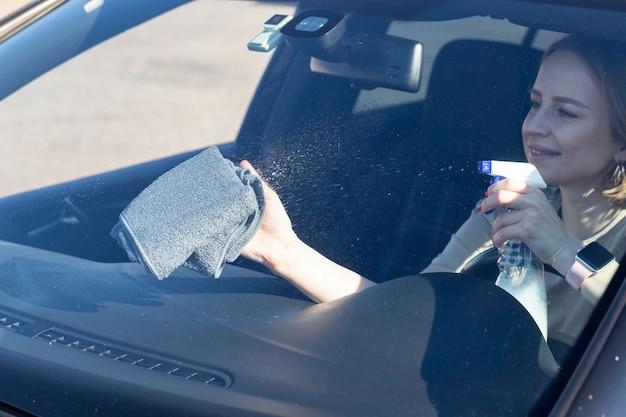 Vrouw bestuurder auto voorruit met spray reinigen, veegt met microfiber van stof en vuil. Premium Foto
