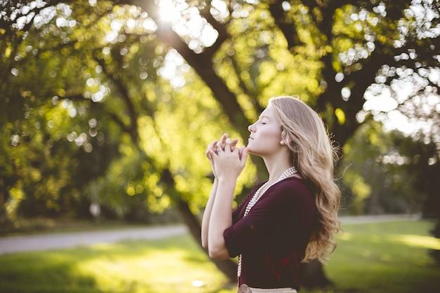 Vrouw bidden onder boom overdag Gratis Foto