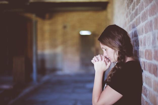 Vrouw bidden terwijl leunend tegen bakstenen muur Gratis Foto