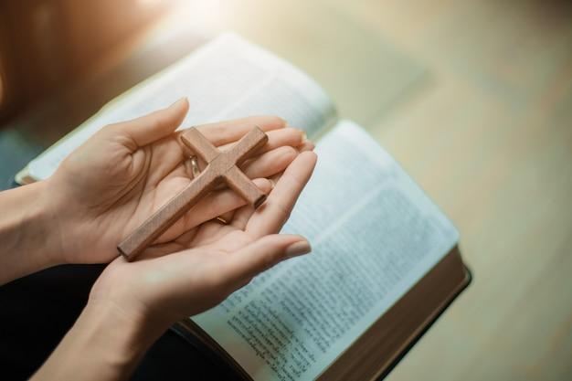 Vrouw bidt met bijbel en houten kruis. Premium Foto