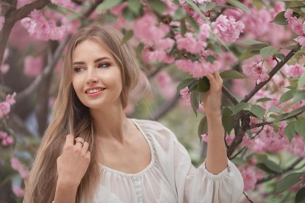 Vrouw bij bloeiende sakura tree op aard Premium Foto