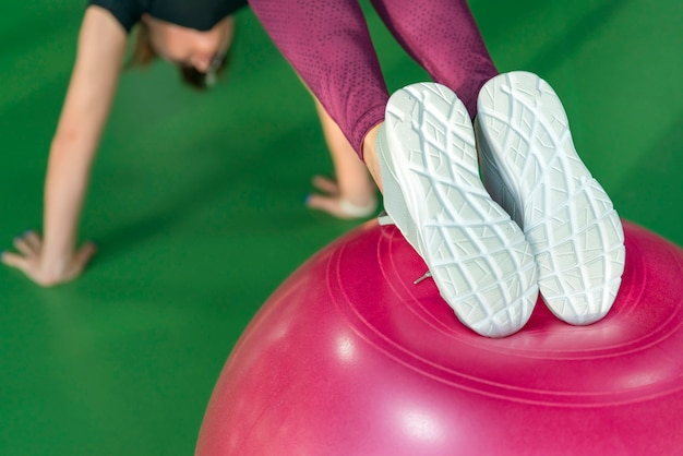 Vrouw bij de gymnastiek die plank met pilatesbal doet Premium Foto