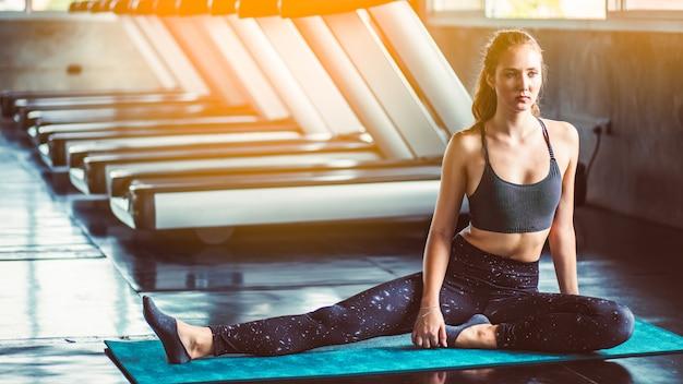 Vrouw bij de gymnastiek die uitrekkende oefeningen doet en op de vloer glimlacht Premium Foto
