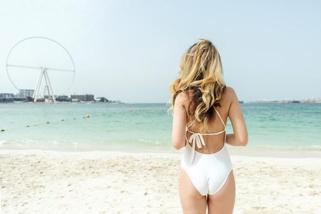 Vrouw bij het strand dat van doubai witte zwempakken draagt Premium Foto