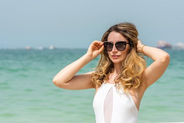 Vrouw bij het strand van dubai in witte zwempakken Premium Foto