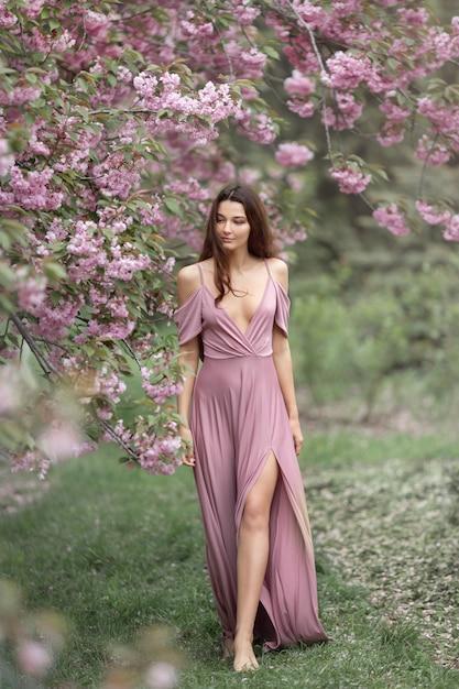 Vrouw bij tot bloei komende sakura-boom op aard Premium Foto