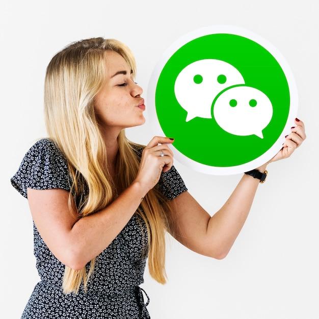 Vrouw blaast een kus op een wechat-pictogram Gratis Foto