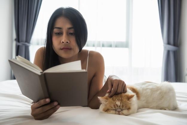 Vrouw boek lezen en spelen kat op bed Premium Foto