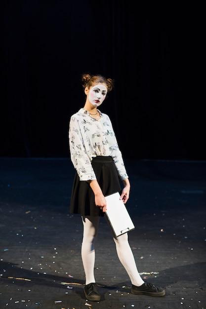 Vrouw bootst met manuscript staande op het podium Gratis Foto