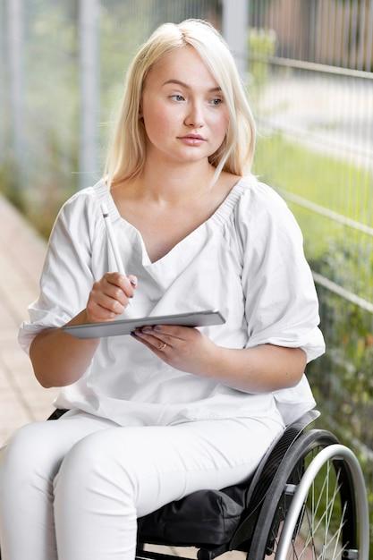 Vrouw buiten in rolstoel met tablet Gratis Foto