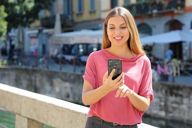 Vrouw chatten met mobiele telefoon op navigli-kanalen in milaan, italië Premium Foto