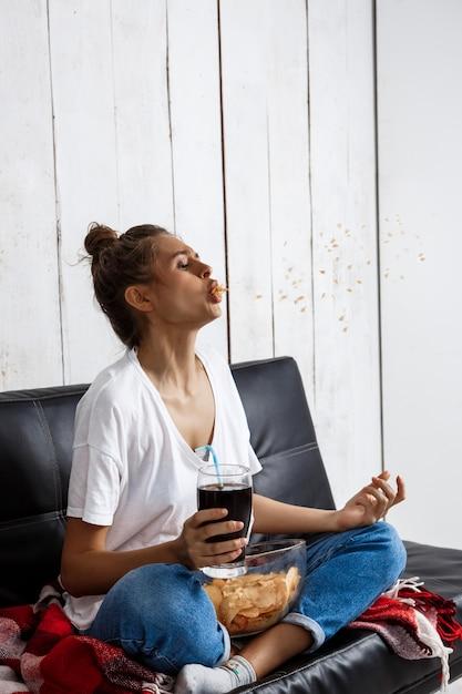 Vrouw chips eten, frisdrank drinken, tv kijken, zittend op de bank. Gratis Foto