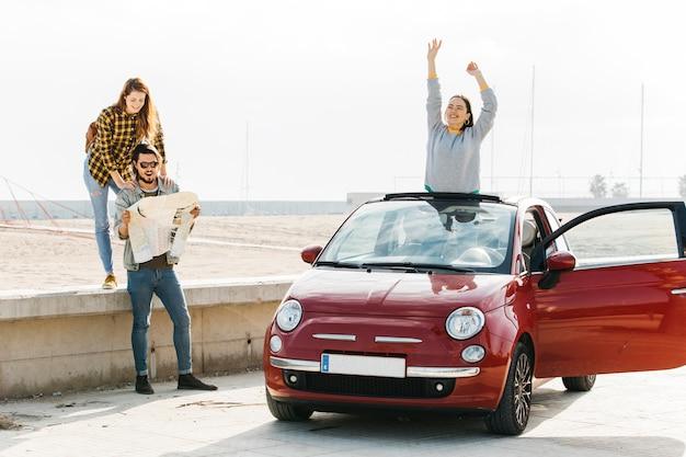 Vrouw dichtbij de mens die kaart en positieve dame bekijken die uit auto dichtbij strand leunen Gratis Foto