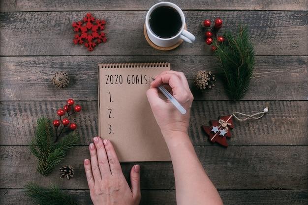 Vrouw die 2020-doelstellingen in notitieboekje met vakantiedecoratie schrijven op houten lijst Premium Foto