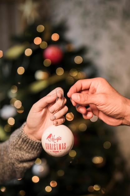 Vrouw die aan de bal van kerstmis van het mensenornament geeft Gratis Foto