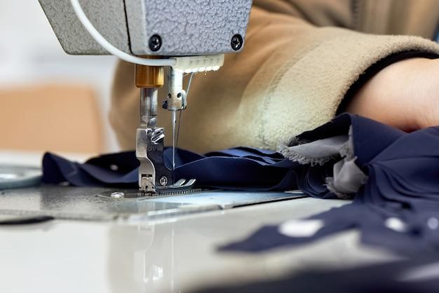 Vrouw die aan een naaimachine werkt met blauwe stof Gratis Foto