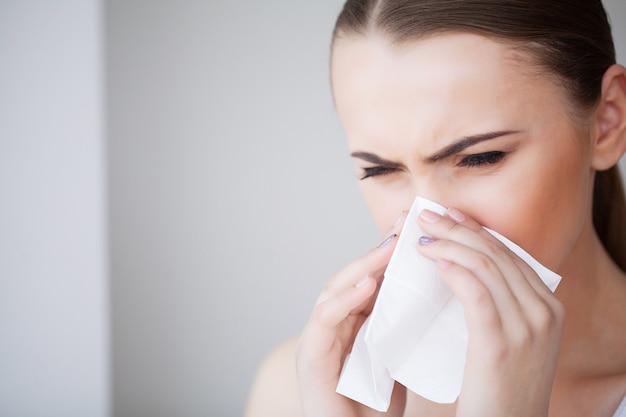 Vrouw die aan koude in huis met weefsel lijden Premium Foto