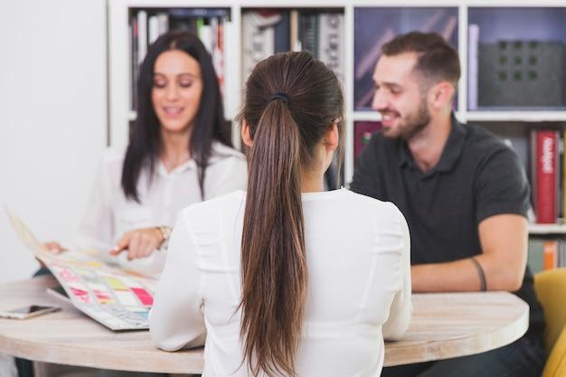 Vrouw die aan mensen in bureau spreekt Gratis Foto