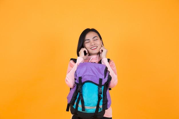Vrouw die aan muziek en schooltas luistert Premium Foto