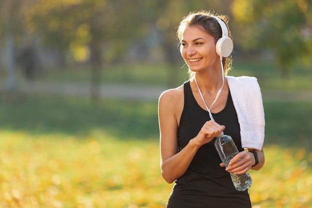 Vrouw die aan muziek luistert en een fles water houdt Gratis Foto