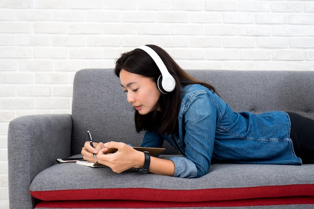 Vrouw die aan muziek luistert en thuis agenda op bank schrijft Premium Foto