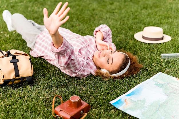Vrouw die aan muziek op hoofdtelefoon op de grond luistert Premium Foto