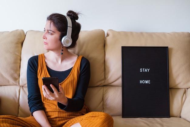 Vrouw die aan muziek thuis met hoofdtelefoons luistert. mensen die besmet zijn met coronavirusziekte op de bank thuis. blijf thuis. pandemische virusziekte covid 19. Premium Foto