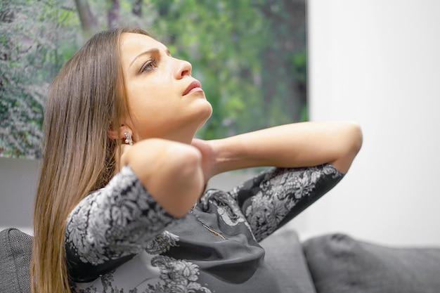 Vrouw die aan nekpijn thuis op laag lijdt. het gevoel van vermoeidheid van de vrouw, uitgeput, gestrest. vermoeide nek. Premium Foto