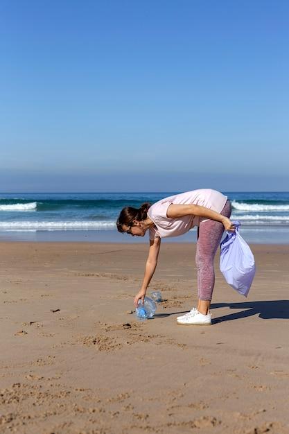 Vrouw die afval en plastieken opnemen die het strand schoonmaken Premium Foto