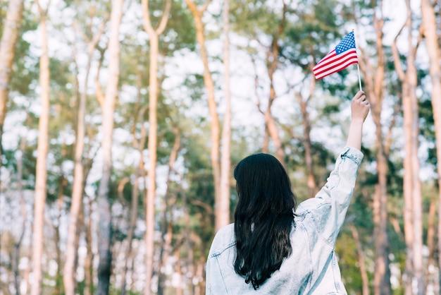 Vrouw die amerikaanse vlag golft Gratis Foto