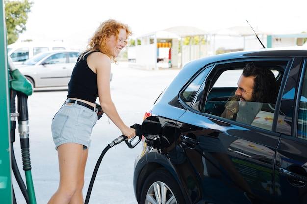 Vrouw die auto opvult en aan vriend bij benzinestation glimlacht Gratis Foto