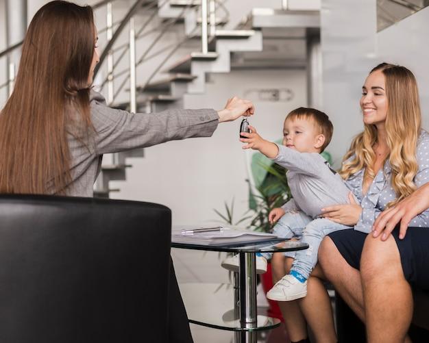 Vrouw die autosleutels geeft aan een baby Gratis Foto