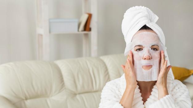 Vrouw die badjas draagt en gezichtsmasker toepast Gratis Foto
