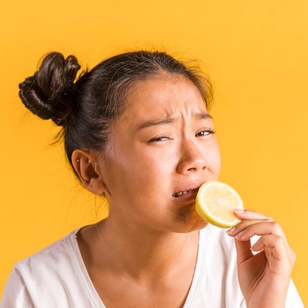 Vrouw die bang is om een citroen te bijten Gratis Foto