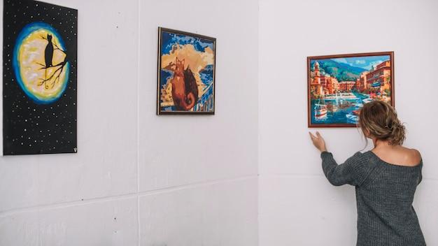 Vrouw die beeld op muur plaatst Gratis Foto