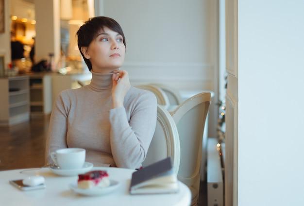 Vrouw die beige colzitting in koffie draagt die door venster kijkt Premium Foto