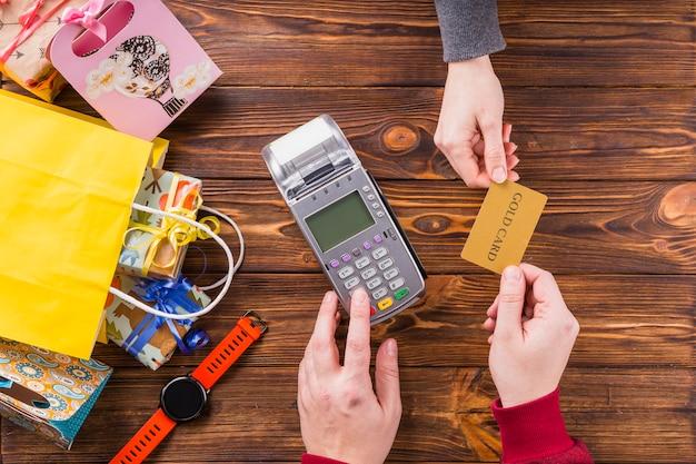 Vrouw die betaalpas aan winkelbediende geeft voor betaling Gratis Foto