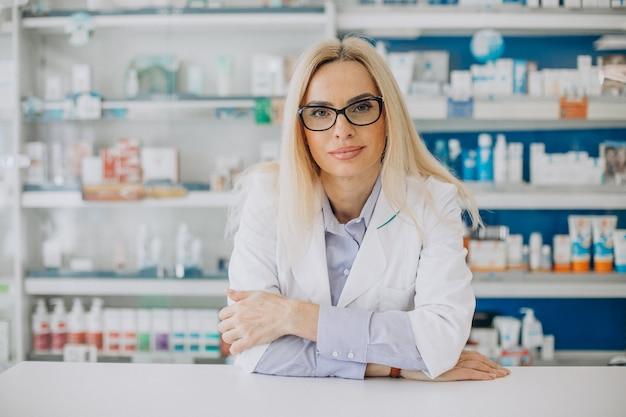Vrouw die bij apotheek werkt en jas draagt Gratis Foto