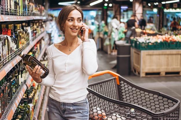 Vrouw die bij de supermarkt winkelt en op telefoon spreekt Gratis Foto