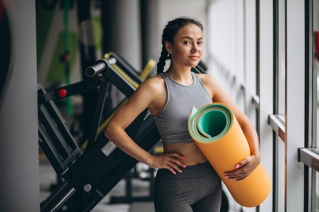 Vrouw die bij de yogamat van de gymnastiekholding uitoefent Gratis Foto