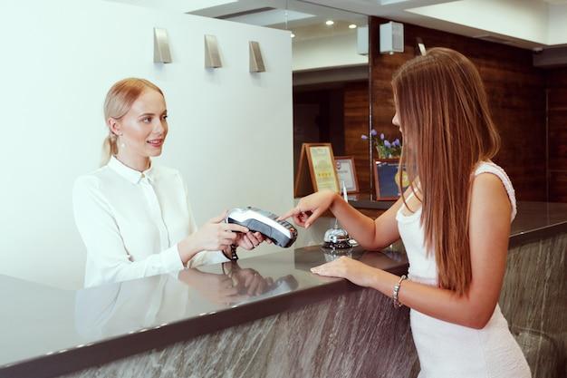 Vrouw die bij hotelontvangst controleert Premium Foto
