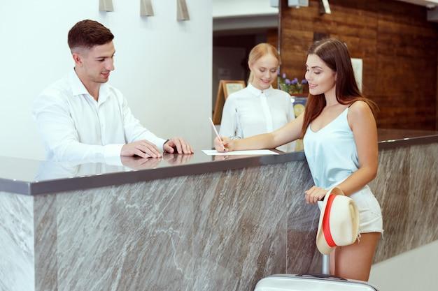 Vrouw die bij hotelontvangst inchecken Premium Foto