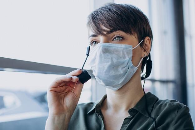 Vrouw die bij verslagstudio werkt en masker draagt Gratis Foto