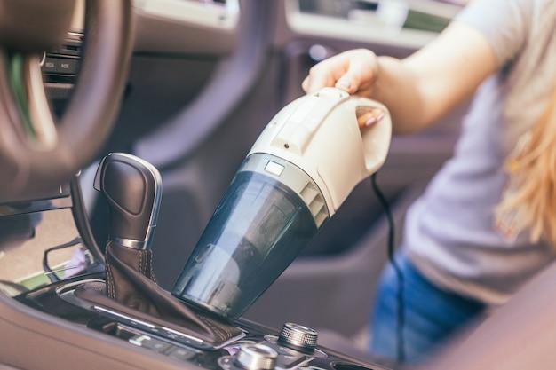 Vrouw die binnenland van auto schoonmaken die stofzuiger met behulp van Premium Foto