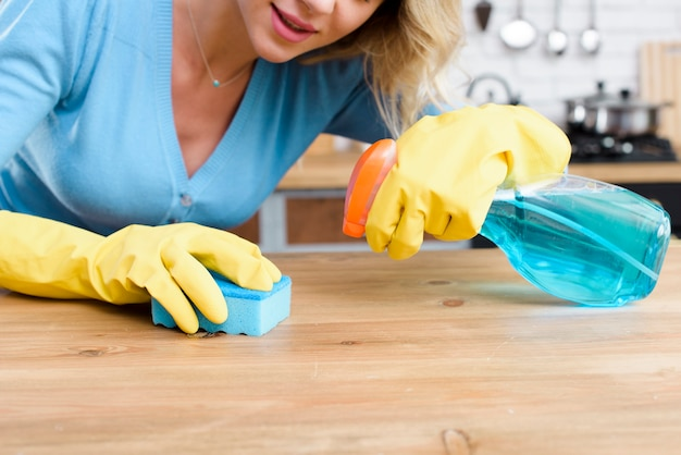 Vrouw die blauwe spons voor het schoonmaken van hout in moderne keuken gebruikt Gratis Foto