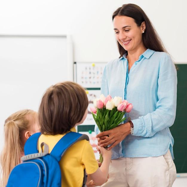 Vrouw die bloemen ontvangt van haar studenten Premium Foto