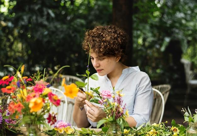 Vrouw die bloemen schikt en verfraait Premium Foto