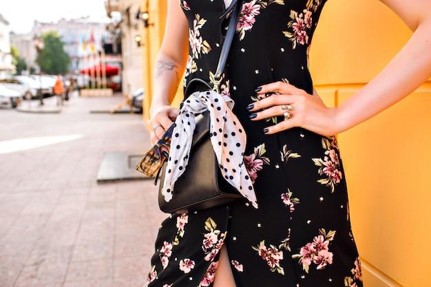 Vrouw die bloemenkleding draagt, die dichtbij gele muur stelt Gratis Foto