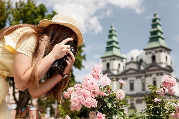 Vrouw die bloemfoto's neemt Gratis Foto